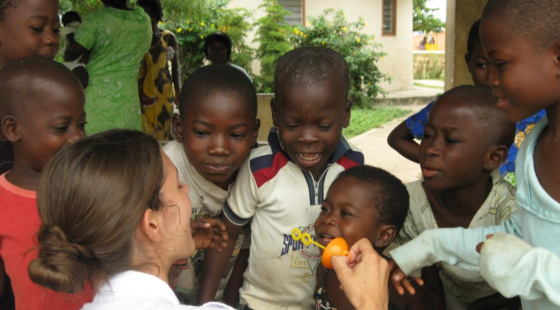 A social work volunteer plays with children and offers them support while doing her internship with Projects Abroad in Ghana.